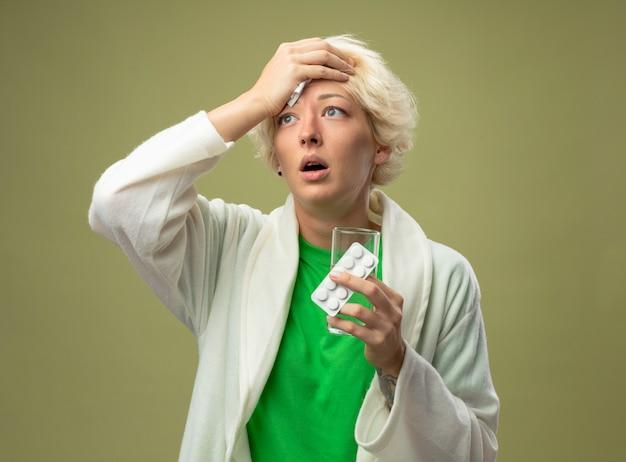 Больная женщина с короткими волосами плохо себя чувствует, держа стакан воды и волдырь с таблетками, касающимися ее лба, стоя над светлой стеной