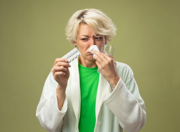 Donna malata con capelli corti sensazione di malessere tenendo un bicchiere di acqua e blister con pillole pulendosi il naso con il tovagliolo in piedi sopra la parete chiara