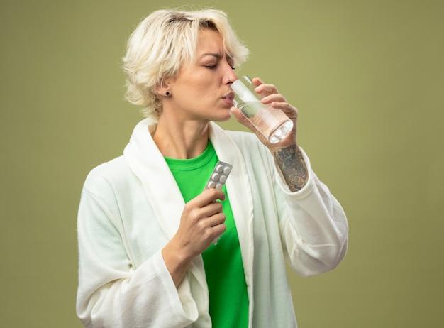 Donna malata con i capelli corti che non si sente bene tenendo un bicchiere d'acqua prendendo medicine in piedi sopra la parete chiara