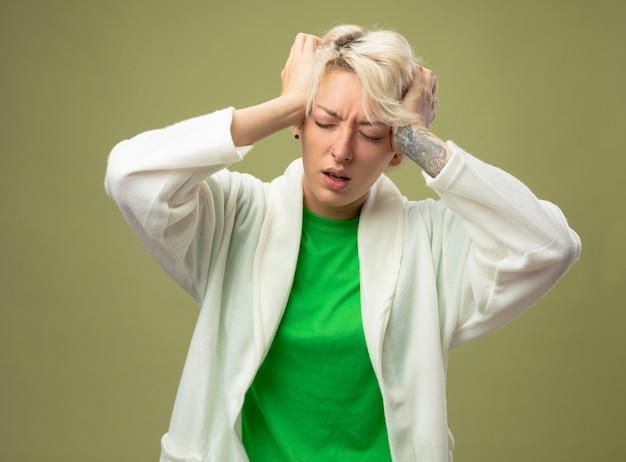밝은 배경 위에 서있는 강한 두통으로 고통받는 그녀의 머리를 만지고있는 짧은 머리를 가진 아픈 여자