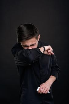 ナプキンを保持し、黒い背景に対して肘の曲がりくねったところに咳をしているコロナウイルスの症状を持つ病気の若いブルネットの男