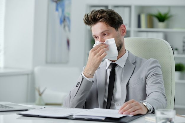 Ill young businessman sitting at desk and rubbing runny nose while working with papers in office, cold and flu concept