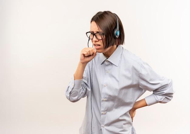 Ragazza malata del call center giovane con gli occhiali e la cuffia avricolare che tiene il pugno vicino alla bocca che tossisce e che mette la mano sulla vita isolata su bianco con lo spazio della copia