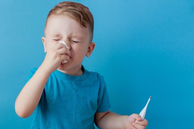 Заболевший маленький ребенок с термометром, измеряет высоту его температуры и смотрит в камеру.