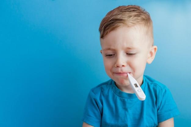 サーモメーターを持った病気の幼い子供。彼の熱の高さを測定し、カメラを見ています。