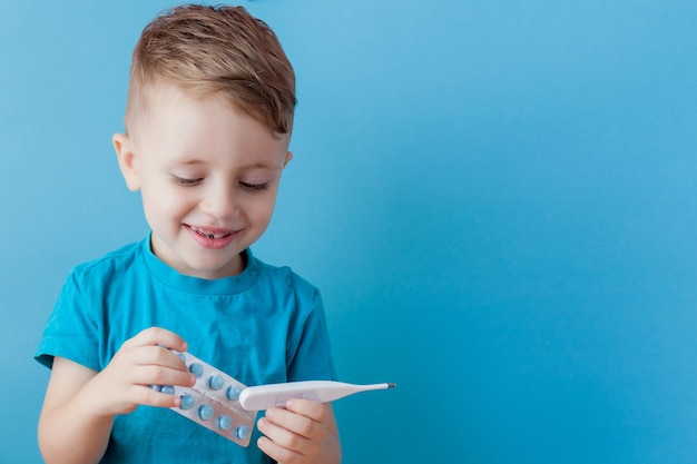Ill young child with a thermomether, measuring the height of his fever and looking