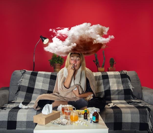 열과 감기에 걸린 아픈 어린 소녀는 고통스러워 보입니다. 아프고, 파랗고, 코를 킁킁거립니다. 아플 때 무게처럼 머리 위의 큰 구름. 감기, 바이러스, 계절 그립. 집에서 소파에 앉아 있는 여자.