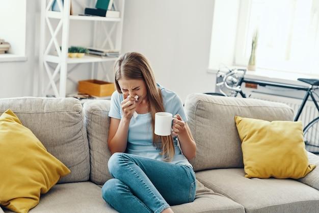 집에서 소파에 앉아있는 동안 코를 불고 재채기를하는 아픈 젊은 여성