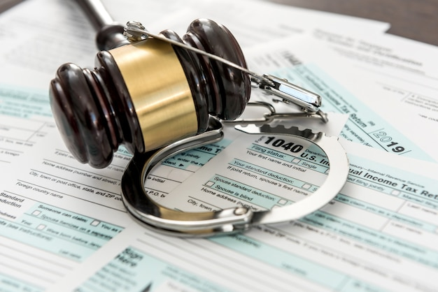 Illegal concept usa tax form with gavel and handcuff. time for business