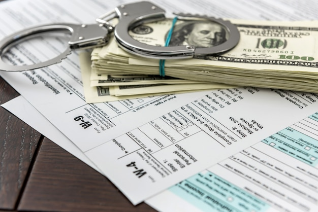 Illegal crime time dollar and handcuff tax form at office