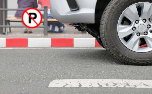 赤のストライプで違法に駐車した車は通りに署名します