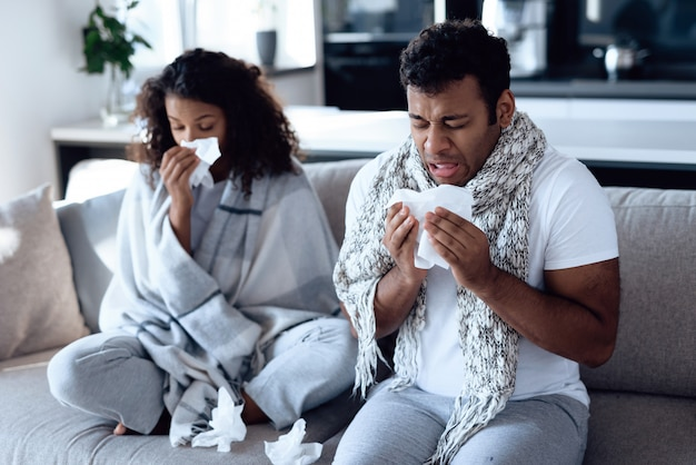 Illness couple with temperature sitting on sofa