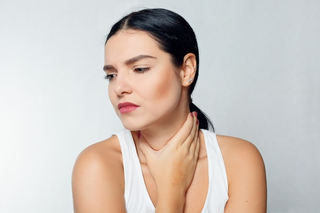 Болезнь, здравоохранение, люди, понятие медицины - боль в горле. крупным планом больная женщина с болью в горле плохо себя чувствует, страдает от болезненного глотания. красивая девушка, касаясь шеи рукой