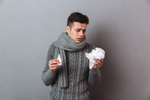 Illness man wearing warm scarf standing isolated