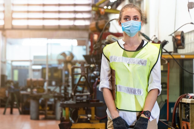 Illness manufacture worker woman with mask cover face stands with the background of indoor factory.