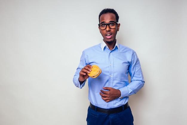 병에 걸린 슬픈 아프리카계 미국인 남자는 세련된 셔츠와 흰색 배경에 햄버거를 들고 안경을 쓴 hamburger.handsome과 젊은 아프리카 남자의 고통스러운 복부에 손을 얹었습니다. 정크 푸드 다이어트 소화 불량.