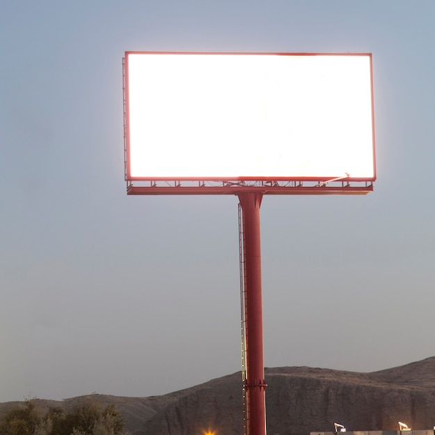 Illuminated blank billboard for advertisement against blue sky