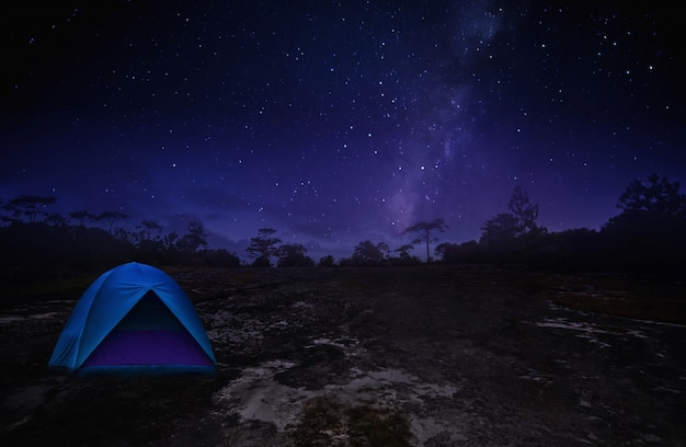 Illuminated blue camping tents of travel camper in starry night with milky way