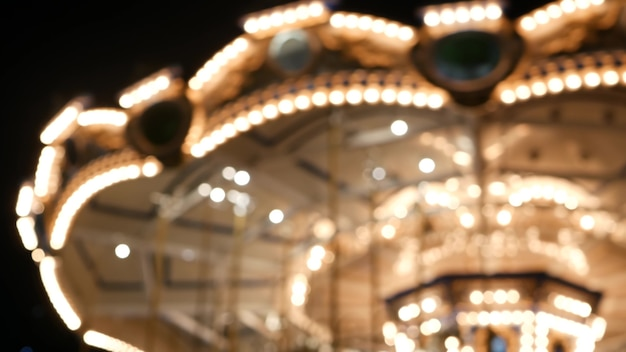 Illuminated blurred merry go round. roundabout spinning, carousel lights in amusement park at night.