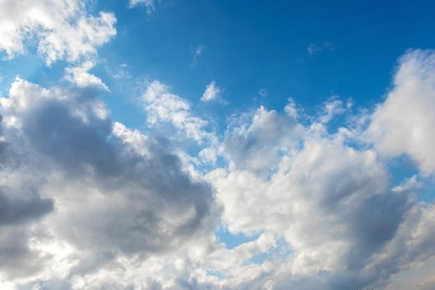 Освещенные солнцем белые облака в голубом небе