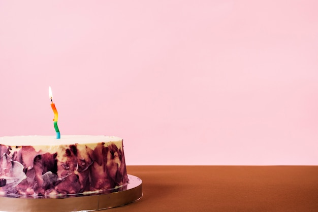 Illuminated candle on delicious cake against pink background