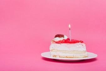 Illuminated candle on birthday cake slice with pink background