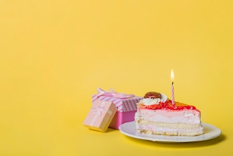 Illuminated candle on slice cake with two gift boxes against yellow background