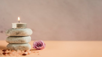 Illuminated candle over the stack of spa stones with himalayan salts and pink rose on colored background