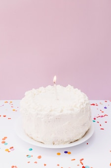 An illuminated candle on white birthday cake over plate against pink background