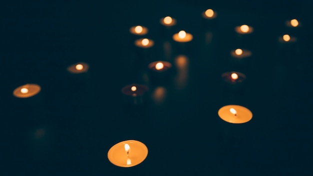 Illuminated candles on black background