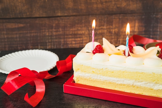 Illuminated candles over the cake with red ribbon and plate on wooden table