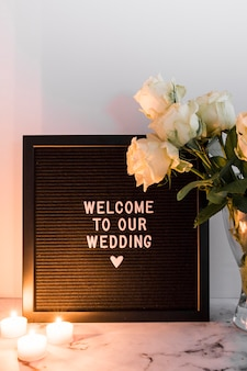 Illuminated candles near the wedding welcome black frame and vase against white backdrop