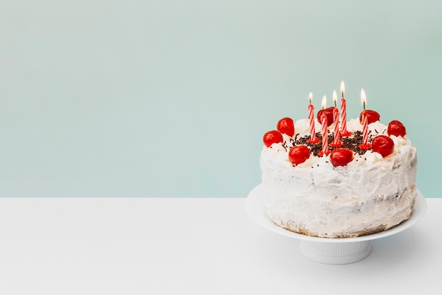 ケーキの上の誕生日ケーキの上の照らされたキャンドルは青い背景に立つ