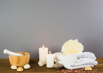 Illuminated candles; towel; spa stones; loofah; mortar and pestle on wooden surface
