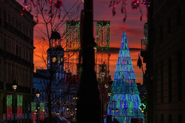 Освещенная рождественская елка растет в центре площади пуэрта-дель-соль в мадриде в сумерках.