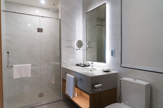 Illuminated contemporary bathroom with clean towels hanging on handles