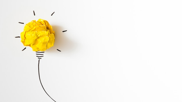 Illuminated crumpled yellow paper light bulb idea on white background