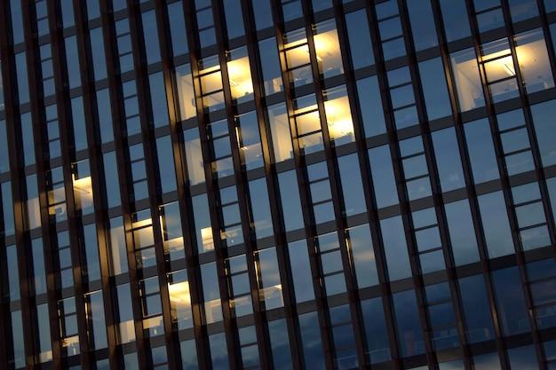 Illuminated empty office building windows in the evening.