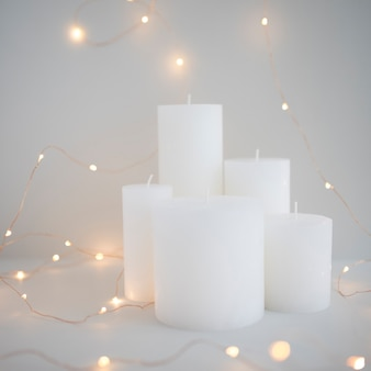 Illuminated fairy lights around white candles on grey background