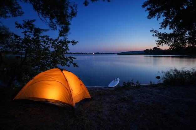 Освещенная изнутри оранжевая палатка и доска для серфинга на пляже