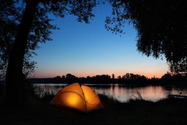 Освещенная изнутри оранжевая палатка на берегу озера среди силуэтов деревьев