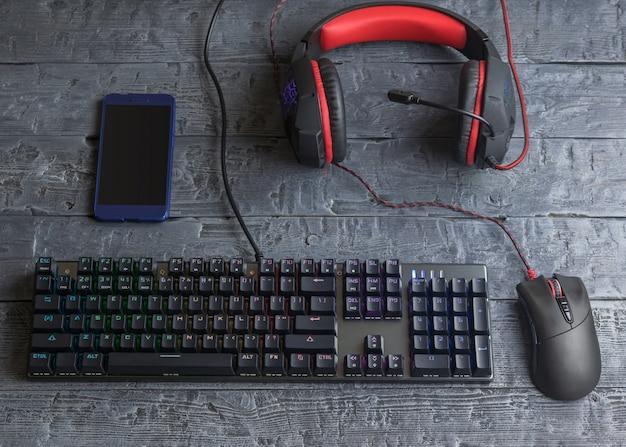 나무 테이블에 조명 된 게임 키보드, 헤드폰 및 마우스