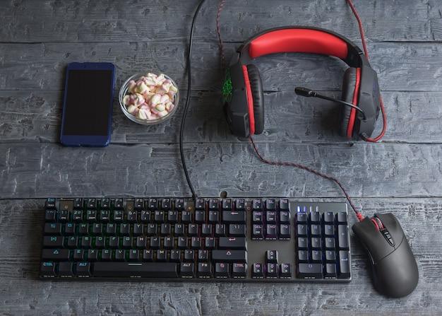 나무 테이블에 조명 된 게임 키보드, 헤드폰, 마우스 및 마시 멜로
