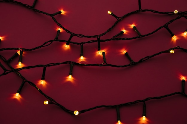 Illuminated garland lights on bright pink background