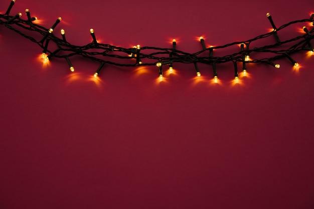 Illuminated garland lights on bright pink background