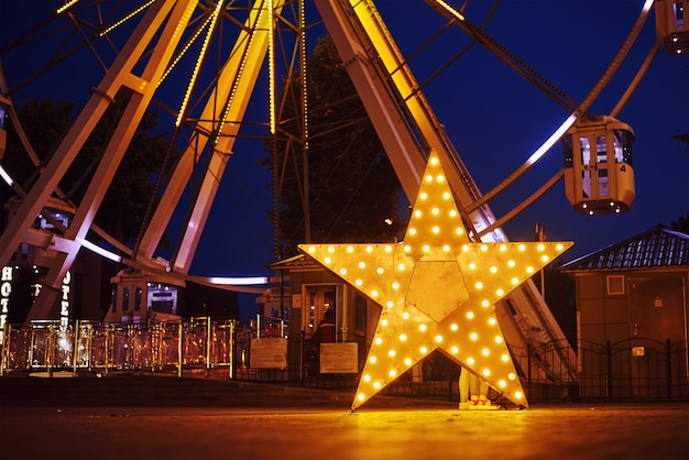 Illuminated glowing star in amusement park at night city
