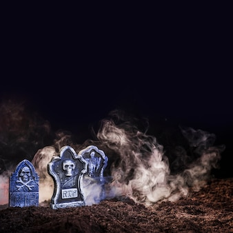 Illuminated gravestones between fog on ground