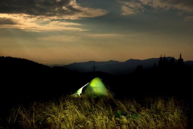 해질녘 들판에 조명이 켜진 녹색 캠핑 텐트