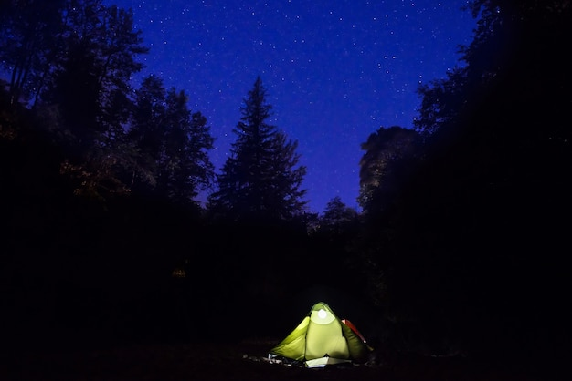 Illuminated green tent at night in the forest under dark blue sky with many stars