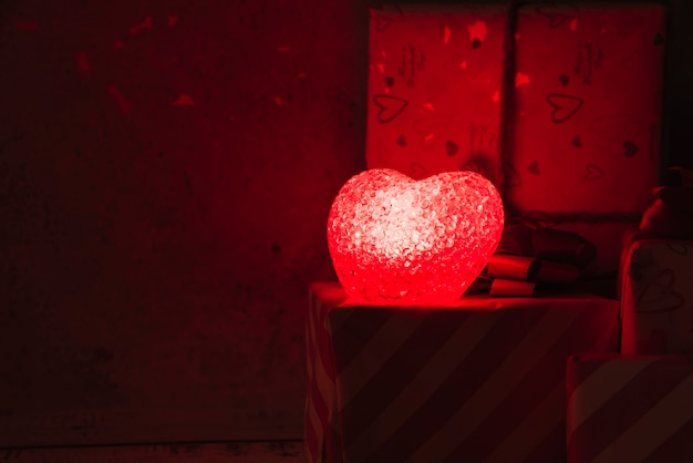 Illuminated lamp in form of heart near present boxes